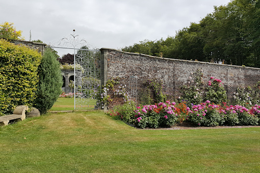 Wemyss walls with clematis, roses and orange alstroemerias©Fiona Woolfenden