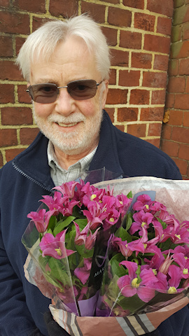 Ken Woolfenden, Editor of the International Clematis Society, holding 2 bunches of C. AMAZING®™ INSPIRATION PBR™©Fiona Woolfenden